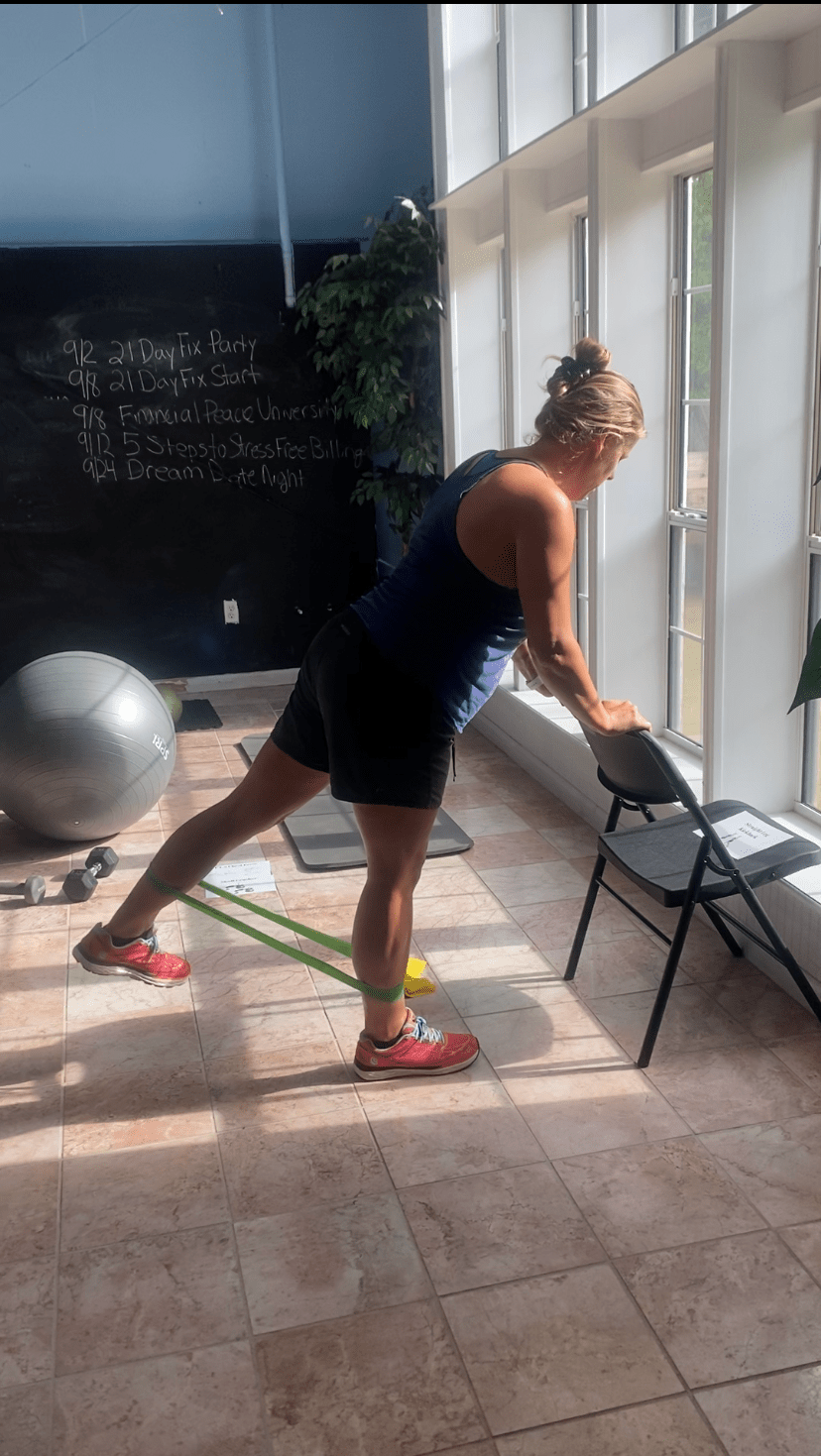 Standing kickbacks can be done at any level. Holding a chair will help you balance, but your feet and legs will still be fighting to keep you upright. Here we've added a band for resistance. The trick to feel this in your booty is to lead with the heel!